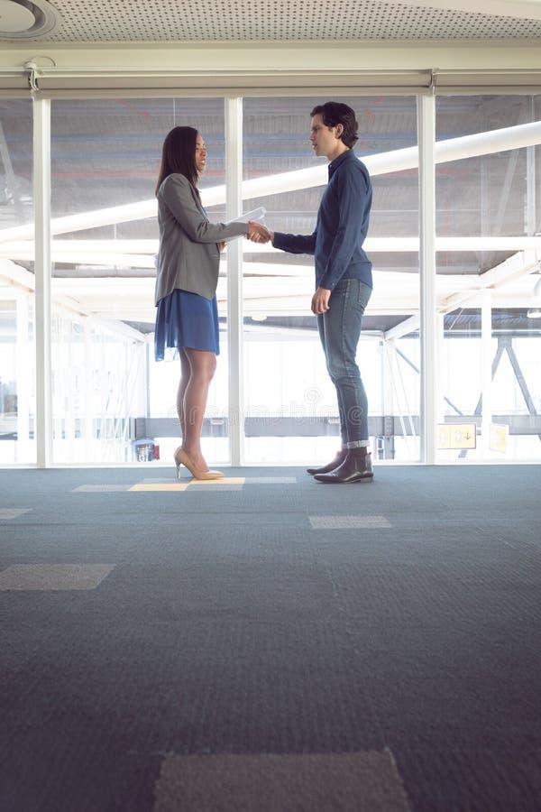 Homem e arquitetos fêmeas que agitam as mãos um com o otro no escritório foto de stock
