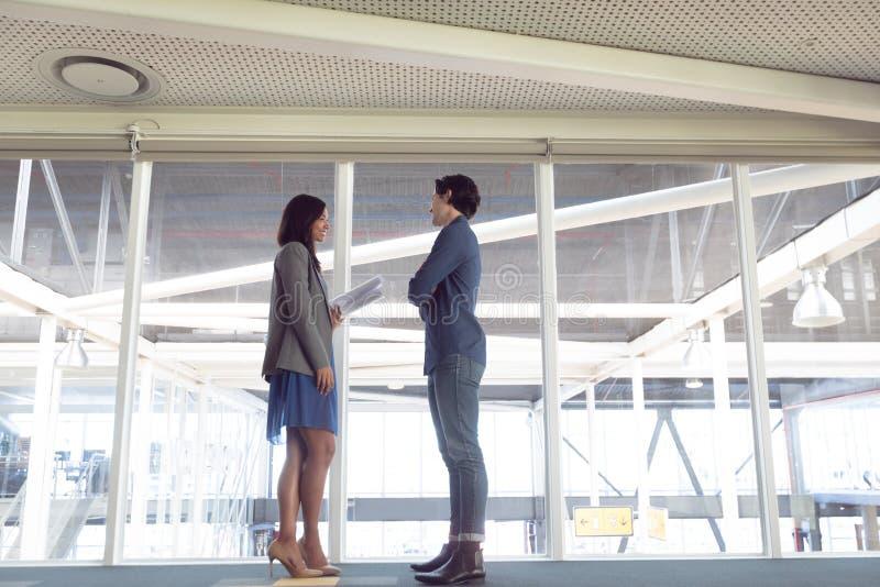 Homem e arquitetos fêmeas que interagem um com o otro no escritório fotografia de stock