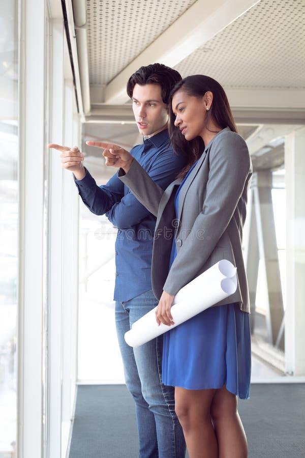 Homem e arquitetos fêmeas que interagem um com o otro no escritório fotos de stock royalty free