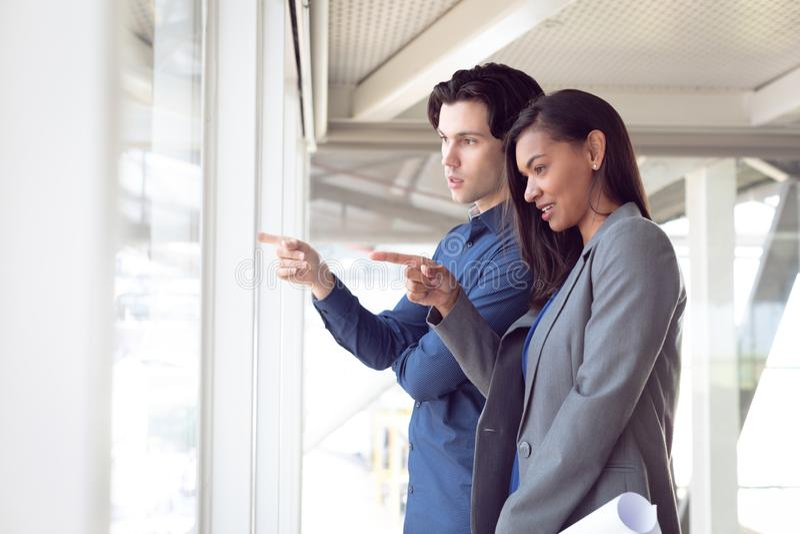 Homem e arquitetos fêmeas que interagem um com o otro no escritório imagem de stock royalty free