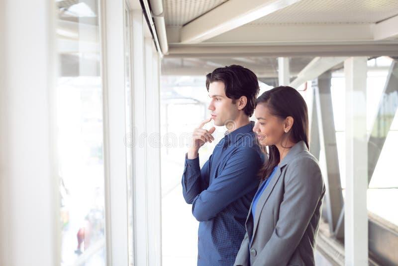 Homem e arquitetos fêmeas que olham através da janela no escritório foto de stock royalty free