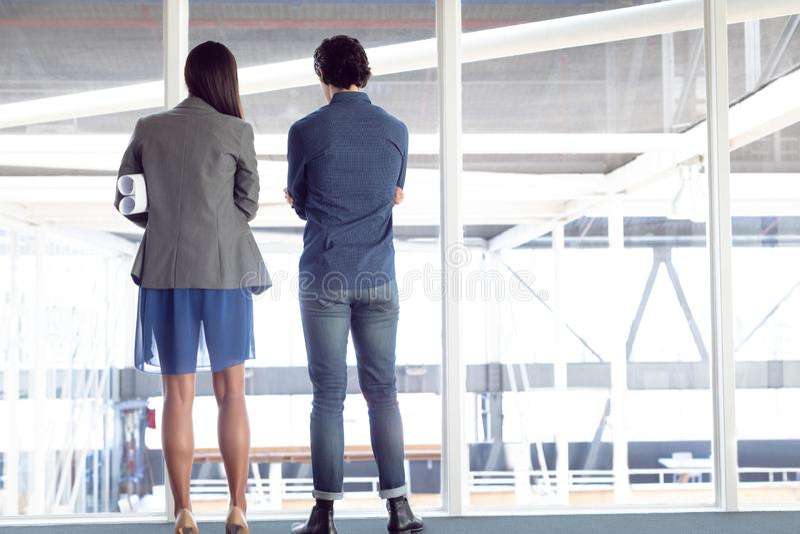 Homem e arquitetos fêmeas que olham através da janela no escritório fotografia de stock
