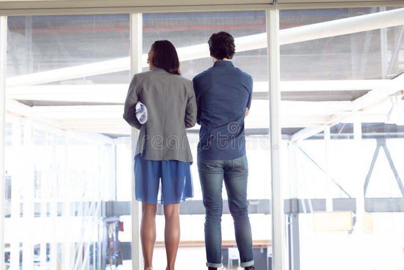 Homem e arquitetos fêmeas que olham através da janela no escritório fotos de stock royalty free