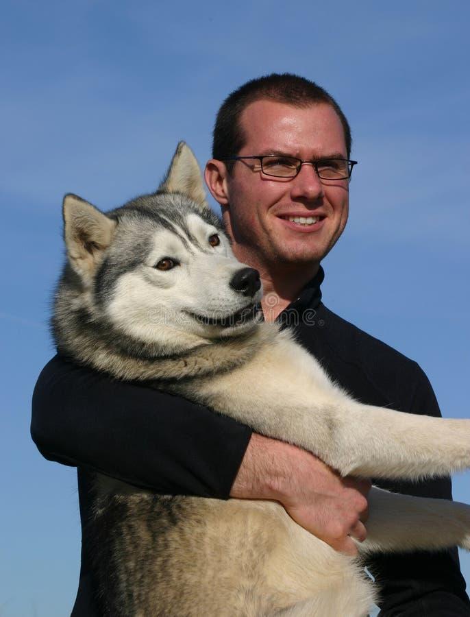Homem e cão de puxar trenós fotos de stock royalty free