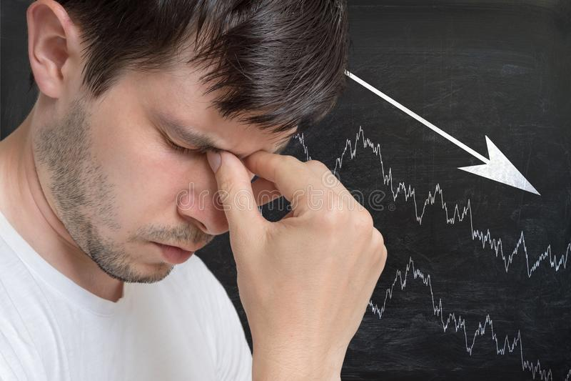 Homem e carta infelizes e desapontados novos com seta para baixo no quadro-negro no fundo fotografia de stock royalty free