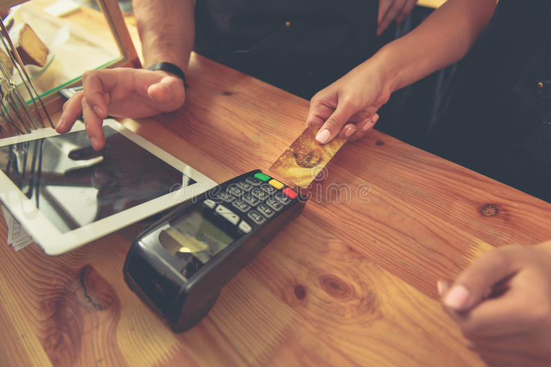 Homem e conta pagando fêmea no café imagem de stock