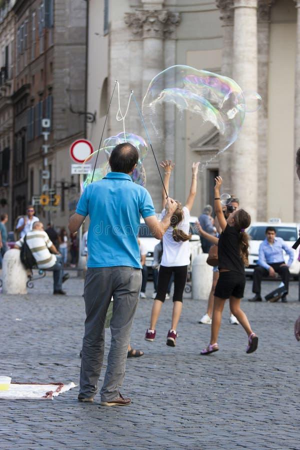 Homem e crianças com grandes bolhas de sabão fotos de stock