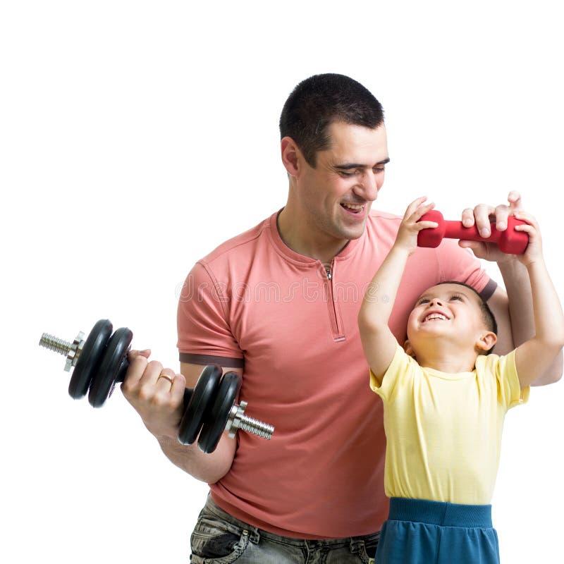 Homem e filho que fazem o exercício com descarga-sinos imagens de stock
