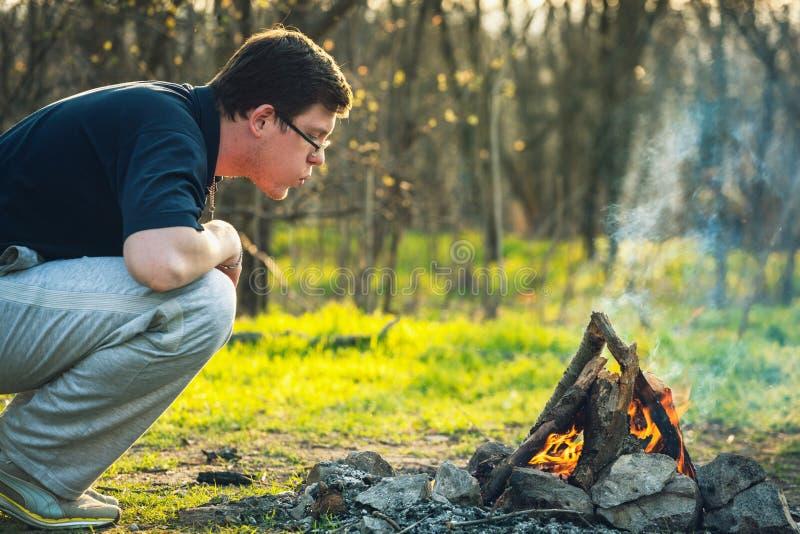 Homem e fogueira em carvões da floresta da mola do fogo Por do sol imagem de stock royalty free