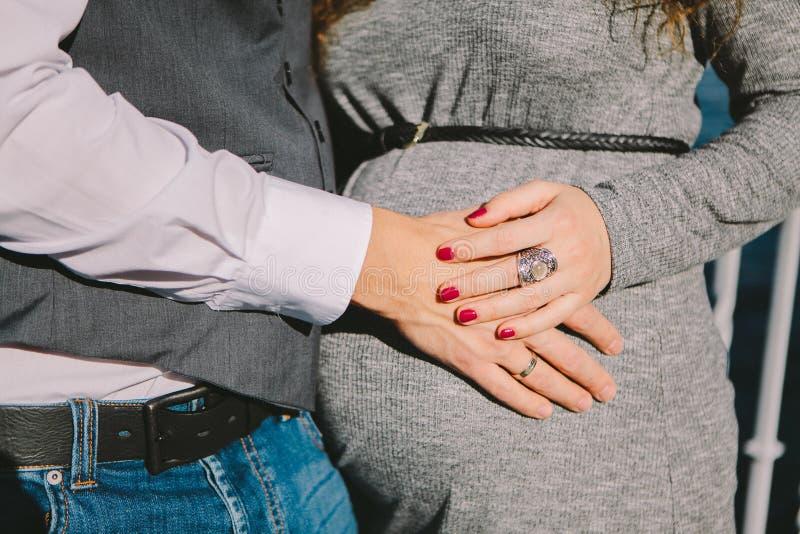 Homem e mão fêmea que afagam a barriga de uma mulher gravida, o conceito de esperar o nascimento da criança, foco seletivo fotos de stock royalty free