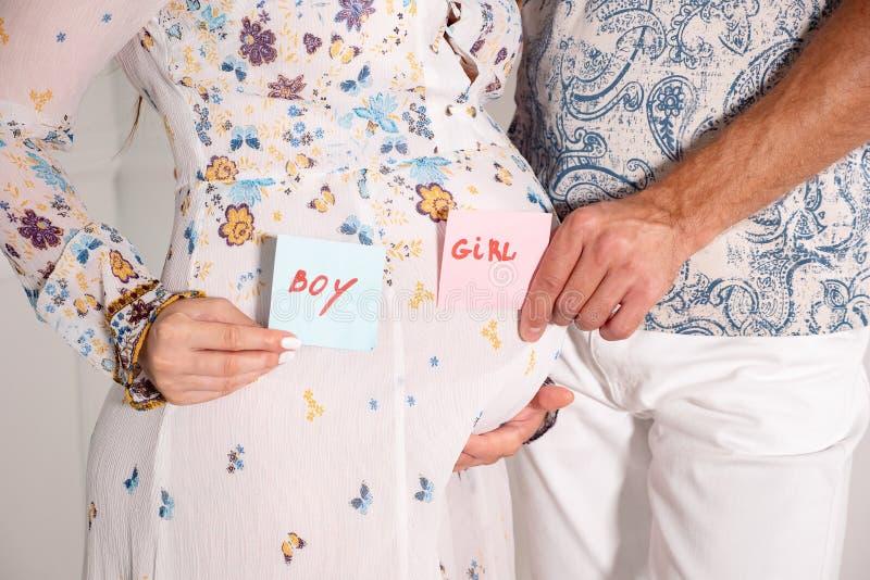 Homem e mãos fêmeas com os cartões do MENINO e da MENINA perto do sino da mulher gravida imagens de stock royalty free
