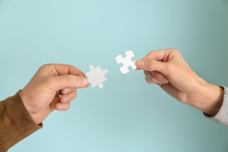 Homem e mãos fêmeas com partes de enigma no fundo da cor fotografia de stock