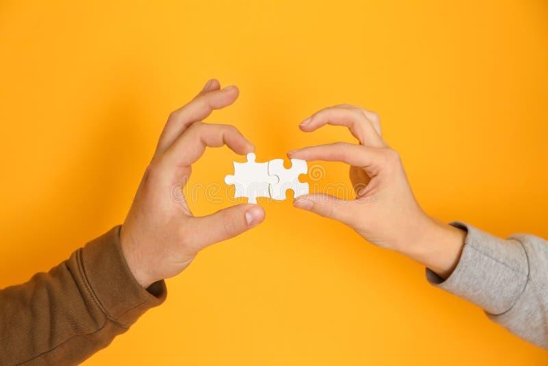 Homem e mãos fêmeas com partes de enigma no fundo da cor foto de stock