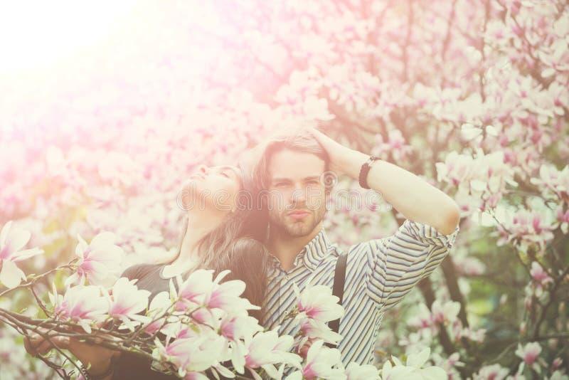 Homem e menina bonita que apreciam a flor da flor da magn?lia fotos de stock royalty free