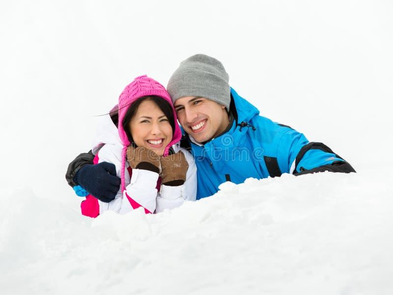 Homem e menina que encontram-se na neve fotografia de stock