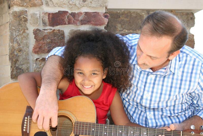 Homem e menina que jogam a guitarra fotografia de stock