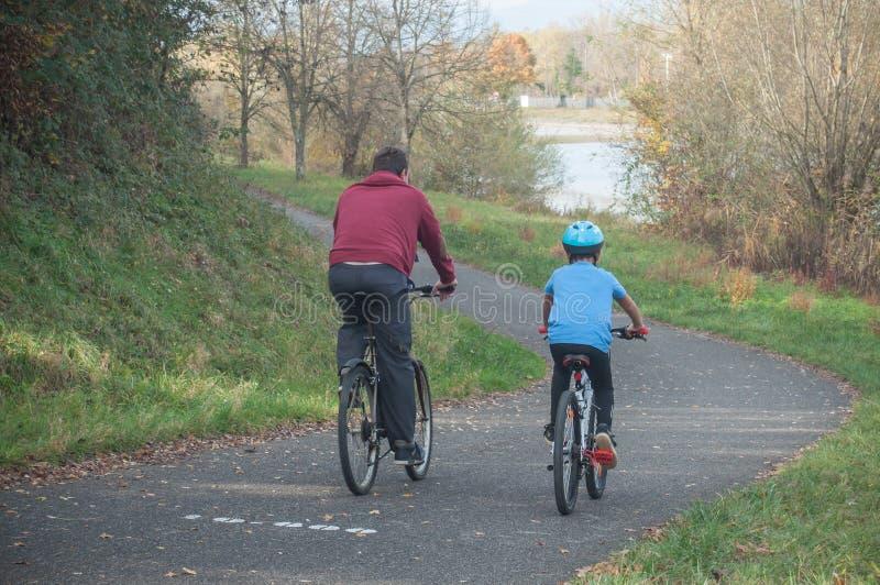 Homem e menino com rolamento da bicicleta na estrada no outono foto de stock