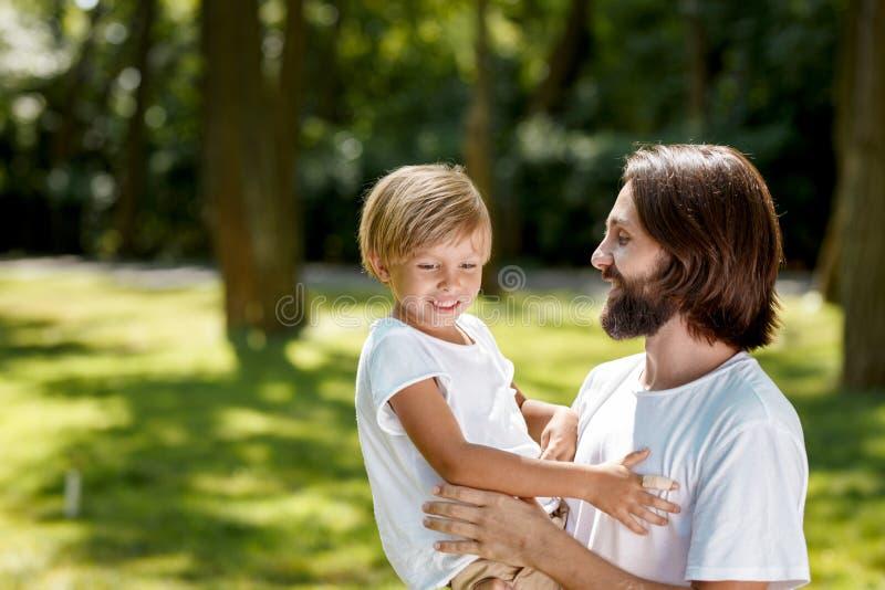 Homem e menino nas camisas brancas de t O homem com cabelo escuro está guardando um menino com cabelo louro em seu menino dos bra fotografia de stock