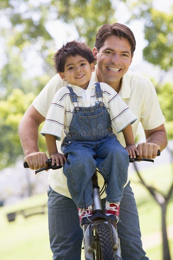 Homem e menino novo em uma bicicleta que sorriem ao ar livre foto de stock