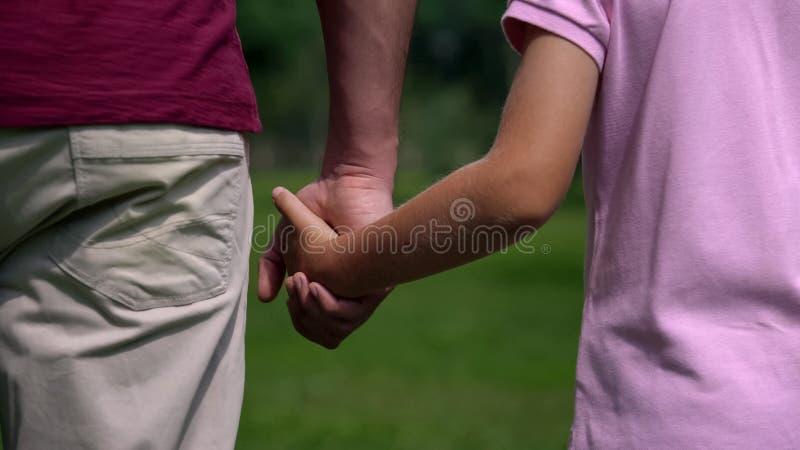 Homem e menino que guardam as mãos e que andam afastado, fim de semana da família no parque, apoio fotografia de stock