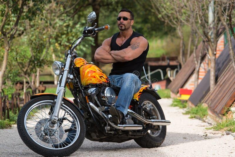 Homem e motocicleta musculares imagem de stock