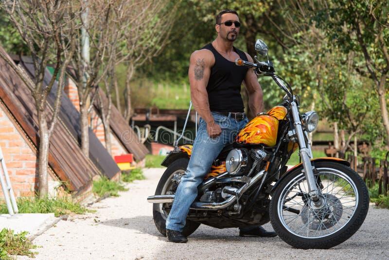 Homem e motocicleta musculares imagens de stock