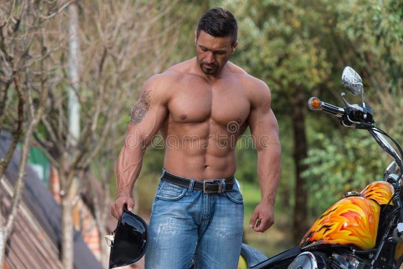 Homem e motocicleta musculares imagens de stock royalty free