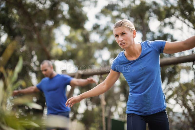 Homem e mulher aptos durante o treinamento do curso de obstáculo foto de stock royalty free