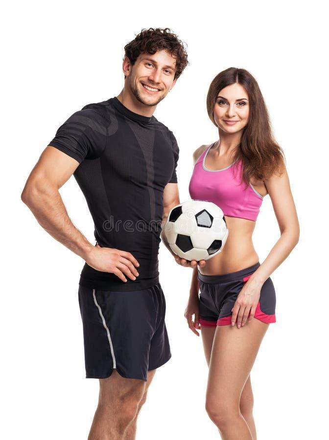 Homem e mulher atléticos com a bola no branco foto de stock royalty free