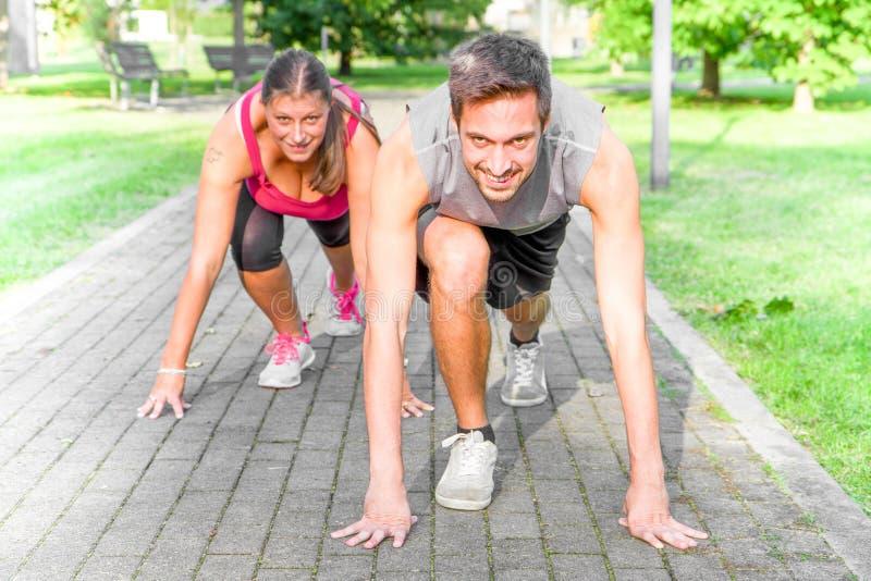 Homem e mulher atléticos consideráveis na posição de começo corredor foto de stock