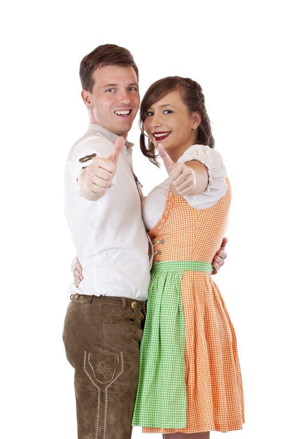 Homem e mulher bávaros com o dirndl que mostra os polegares imagens de stock royalty free