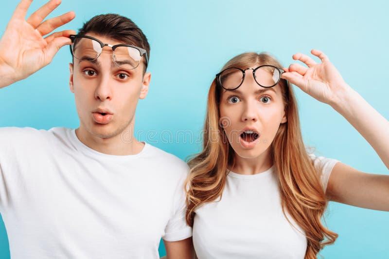 Homem e mulher, chocados pelos olhos largos, bocas, endireitando vidros, em um fundo azul imagem de stock