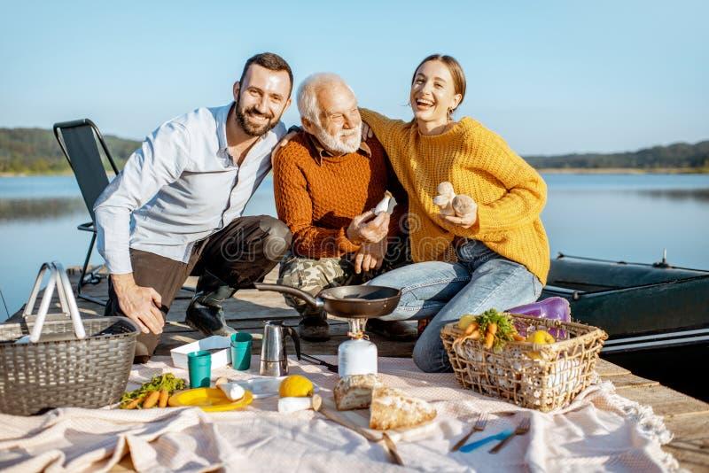 Homem e mulher com o avô superior no piquenique fora imagem de stock
