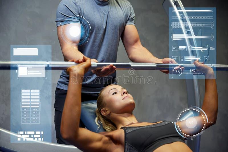 Homem e mulher com o barbell que dobra os músculos no gym imagens de stock