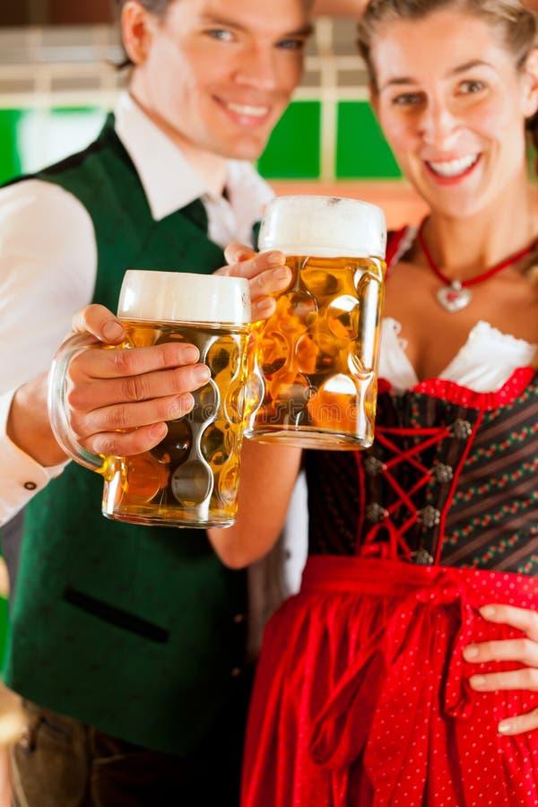Homem e mulher com vidro de cerveja na cervejaria fotografia de stock royalty free