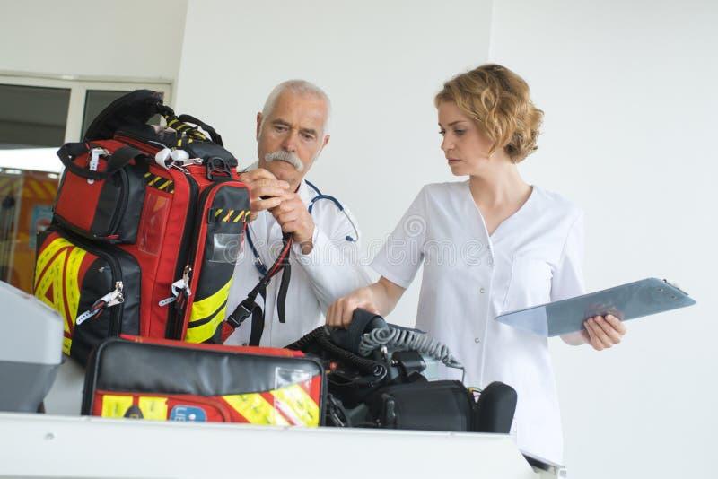 Homem e mulher da ambulância que verificam a engrenagem entre intervenções imagem de stock royalty free