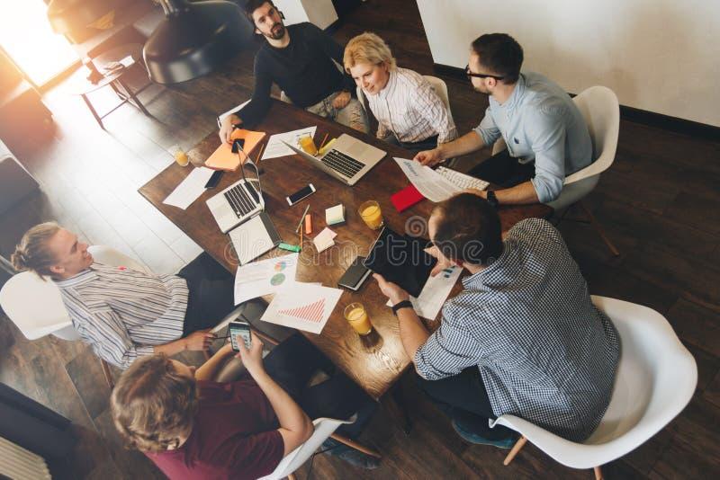 Homem e mulher de negócio que sentam-se em torno da tabela no escritório e no workin fotografia de stock royalty free