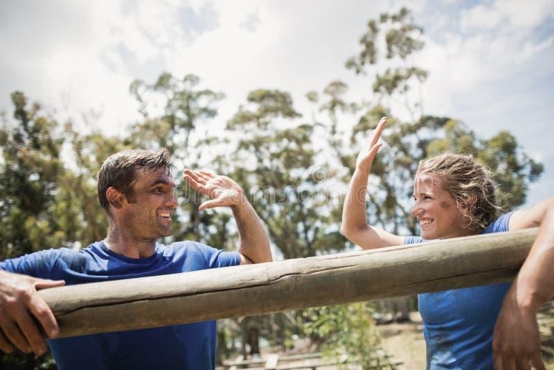 Homem e mulher de sorriso que dão a elevação cinco ao inclinar-se em um obstáculo foto de stock royalty free
