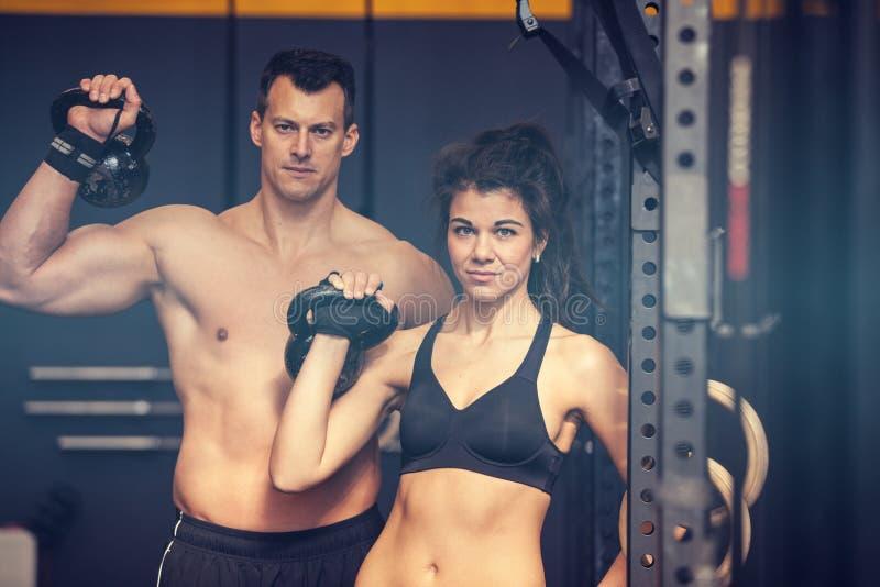 Homem e mulher do treinamento de Kettlebell em um gym fotos de stock royalty free