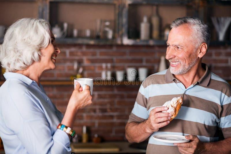 Homem e mulher em seus anos sessenta que dizem gracejos na cozinha foto de stock royalty free