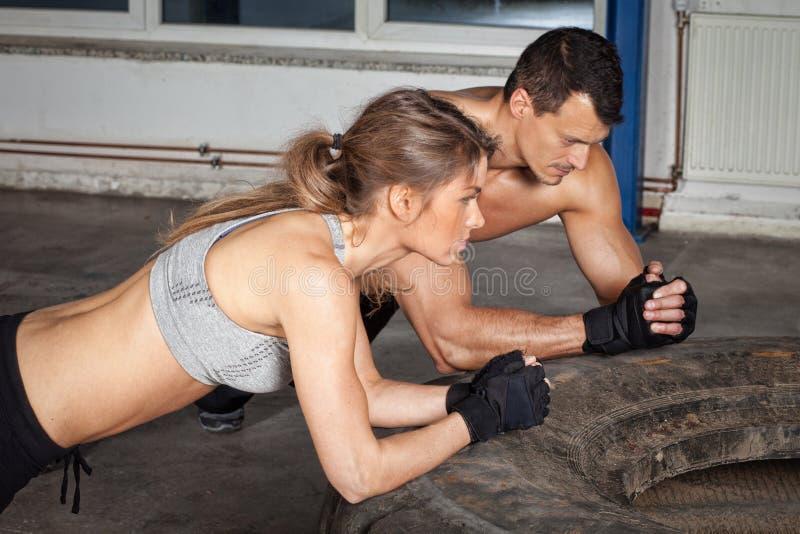 Homem e mulher em um treinamento da aptidão do crossfit do pneu foto de stock
