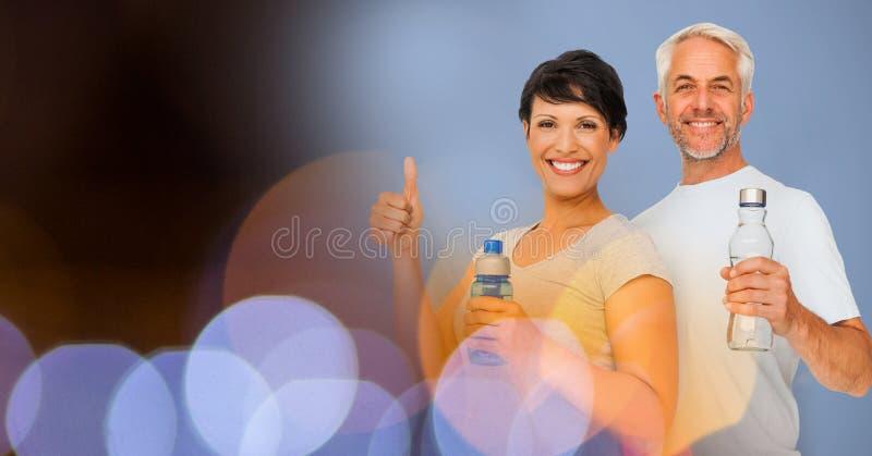 Homem e mulher felizes com as garrafas de água pelo bokeh imagem de stock