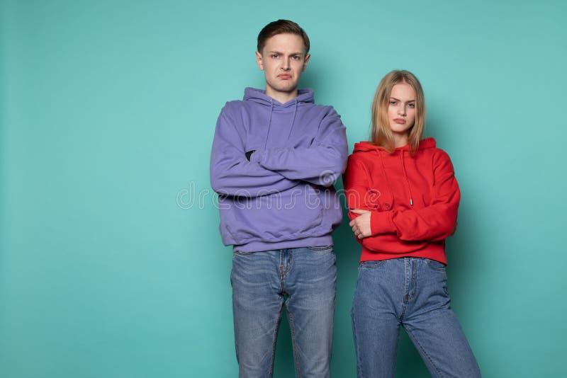 Homem e mulher irritados infelizes dos povos na roupa ocasional, estando junto contra a parede azul no estúdio foto de stock royalty free