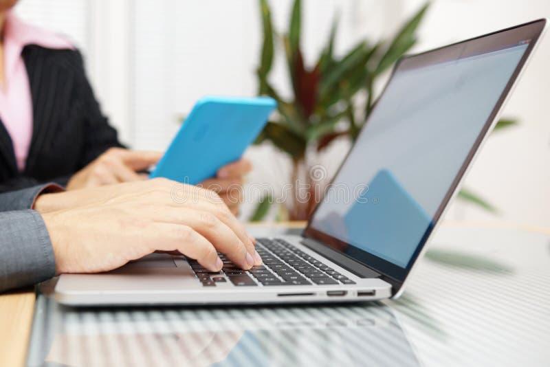 Homem e mulher na reunião de negócios que trabalha no PC e no lapto da tabuleta imagens de stock royalty free