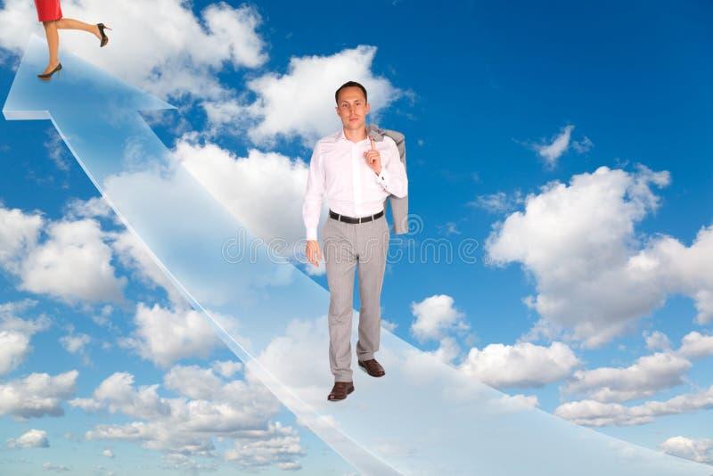 Homem e mulher na seta no céu fotos de stock