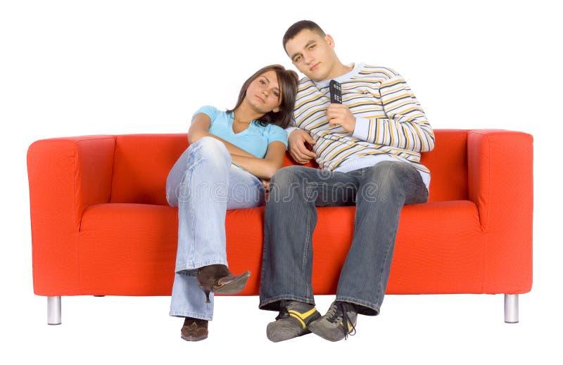 Homem e mulher na televisão de observação do sofá imagens de stock royalty free