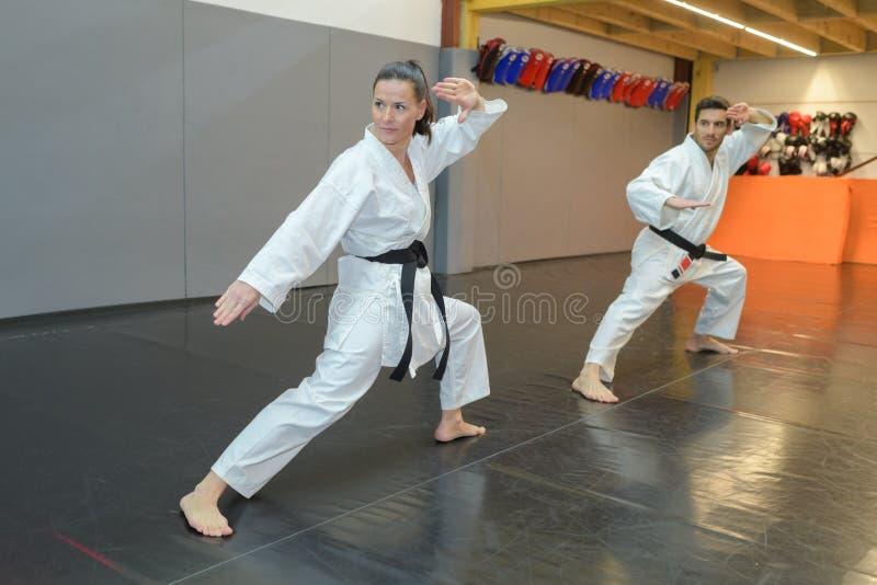Homem e mulher no karaté branco do treinamento do cinturão negro do quimono imagem de stock