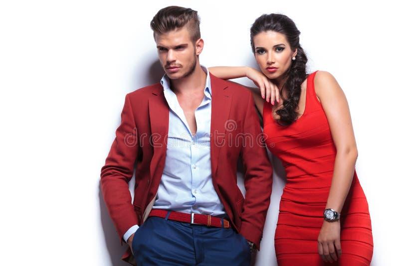 Homem e mulher novos da fôrma contra a parede branca foto de stock
