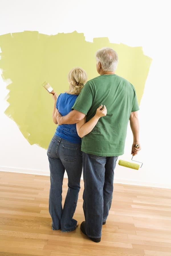 Homem e mulher observando o trabalho da pintura. fotos de stock