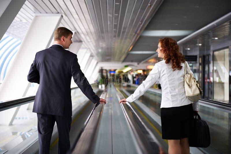 Homem e mulher que andam na escada rolante fotografia de stock